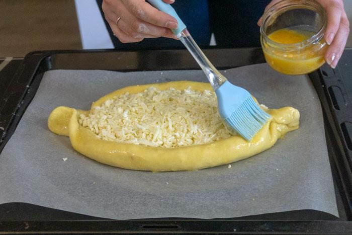 Applying egg wash to the khachapuri